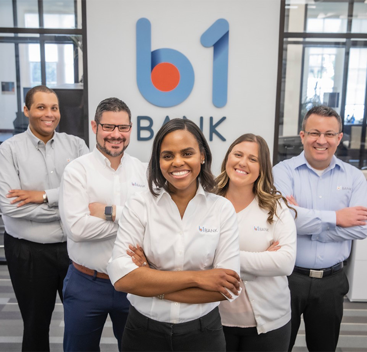 group of employees standing in front of a b1BANK sign