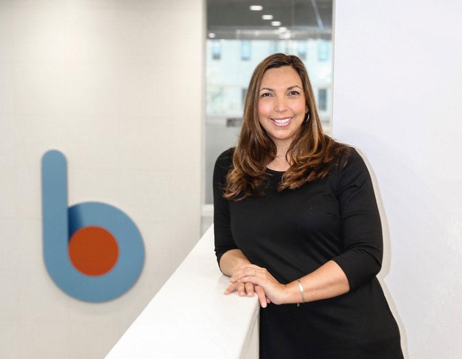 lady in black dress standing next to b1bank logo