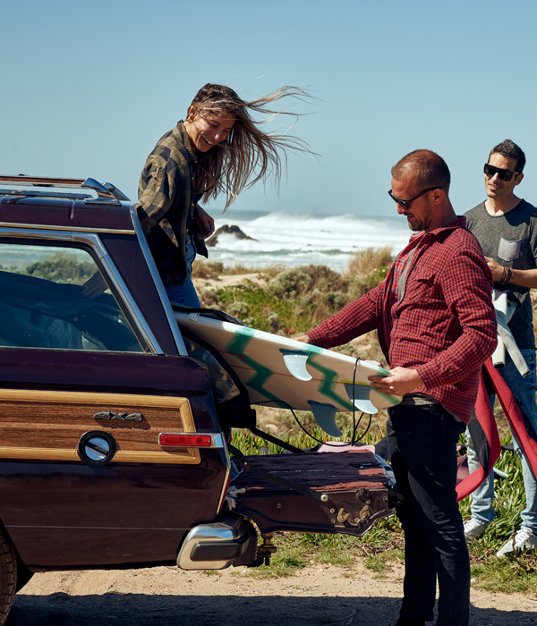 man loading surf board into trunk