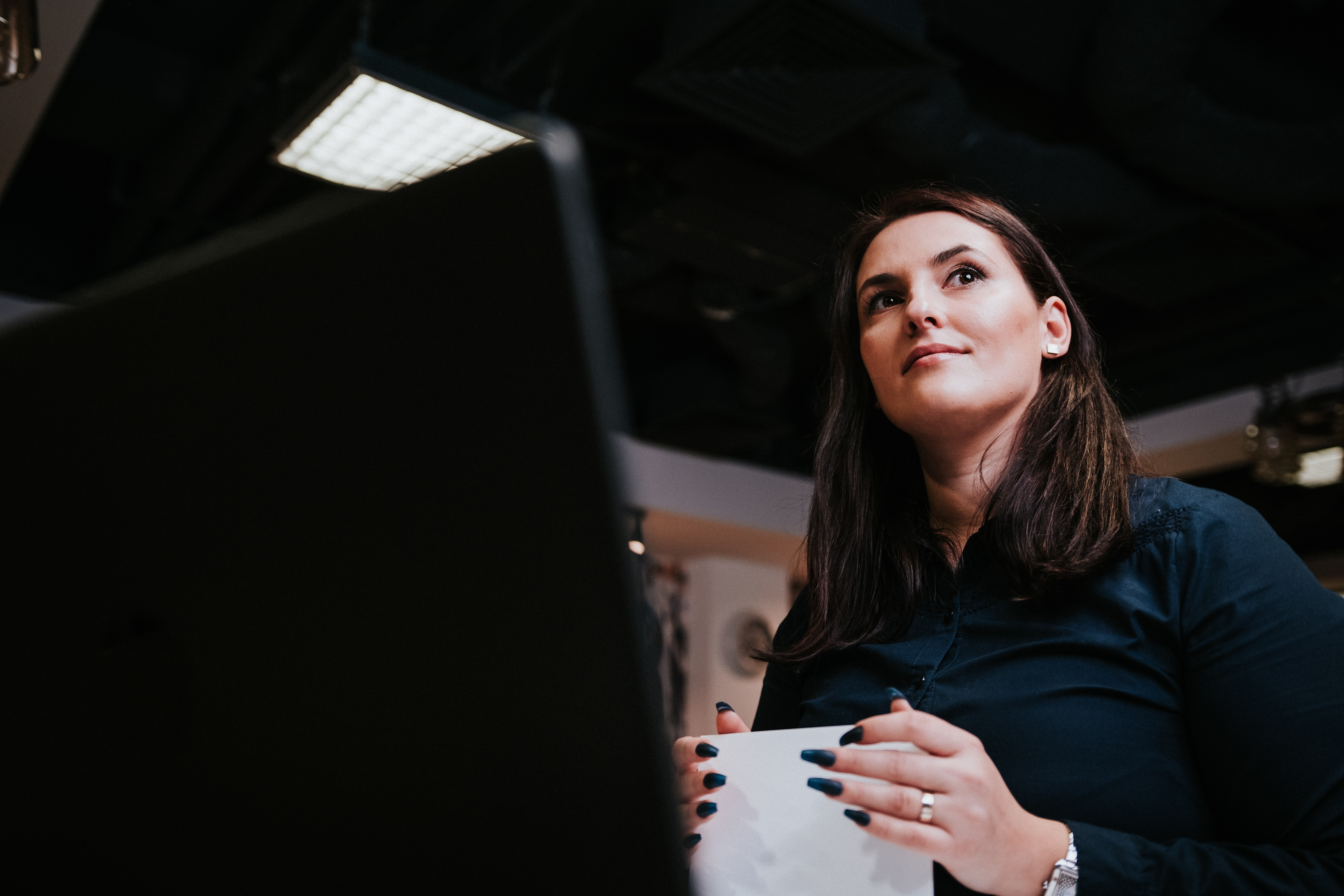Woman in office looks away confidently