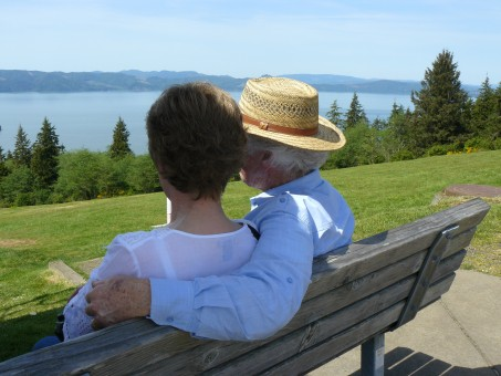 Older white couple on bench near river