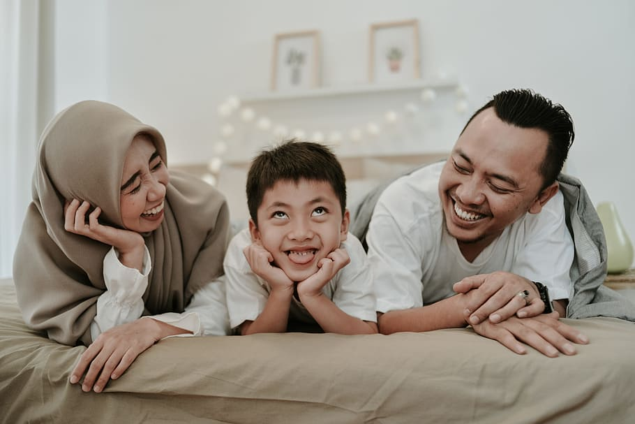 Happy parents and child of color on bed