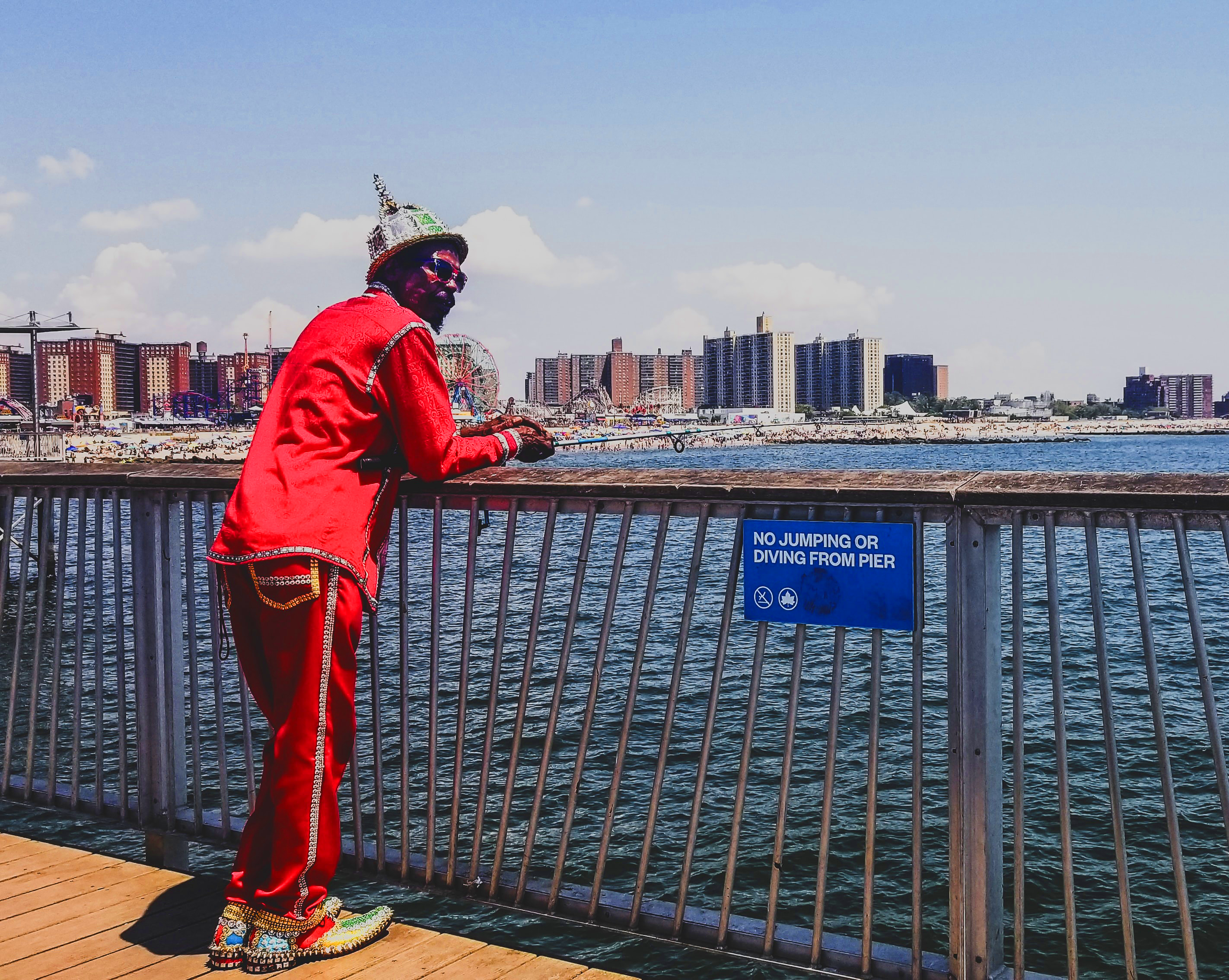 Black man in red jumpsuit looks out over pier at hotels and amusement park