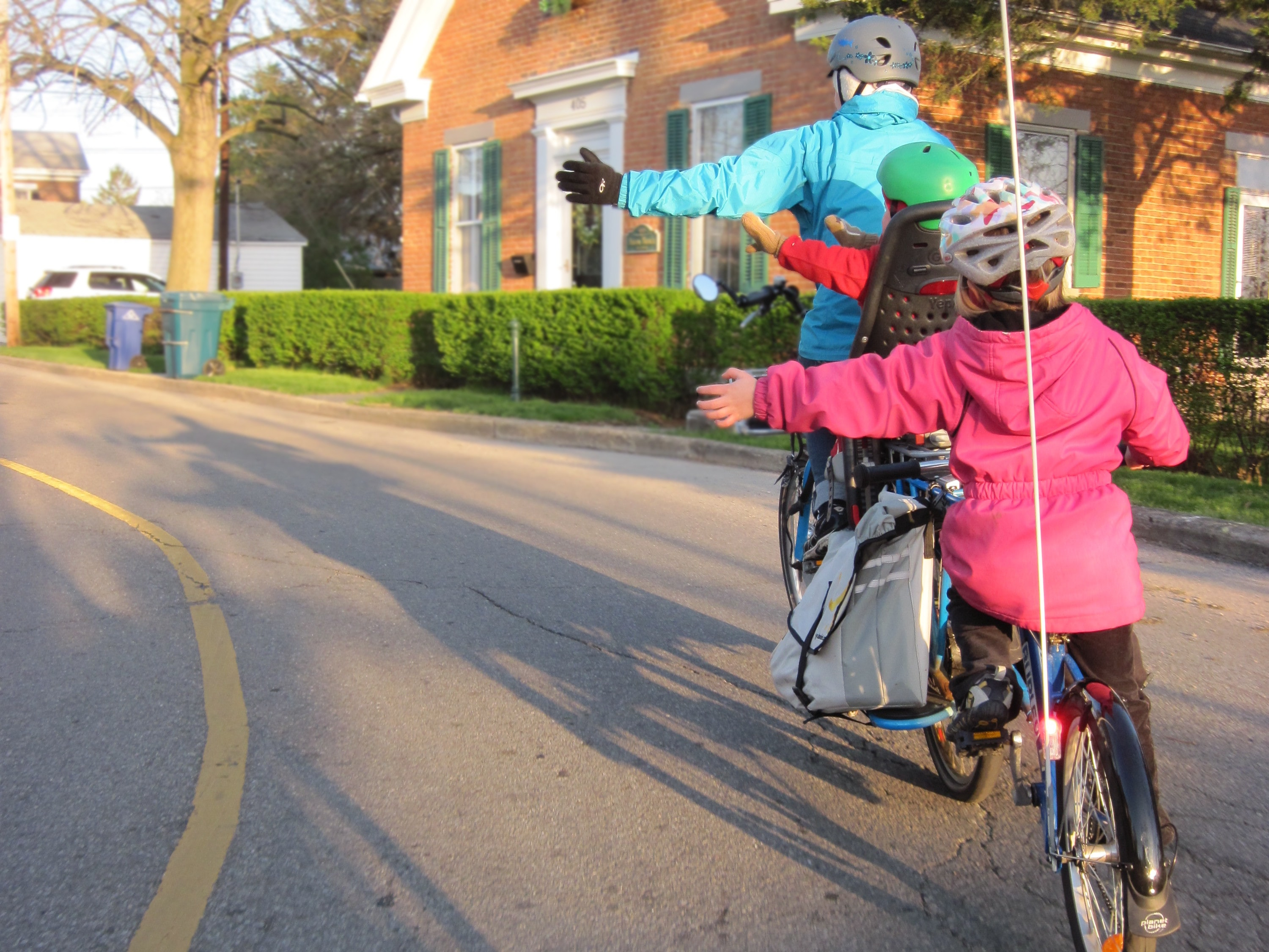 Parent and children riding bicycles near house