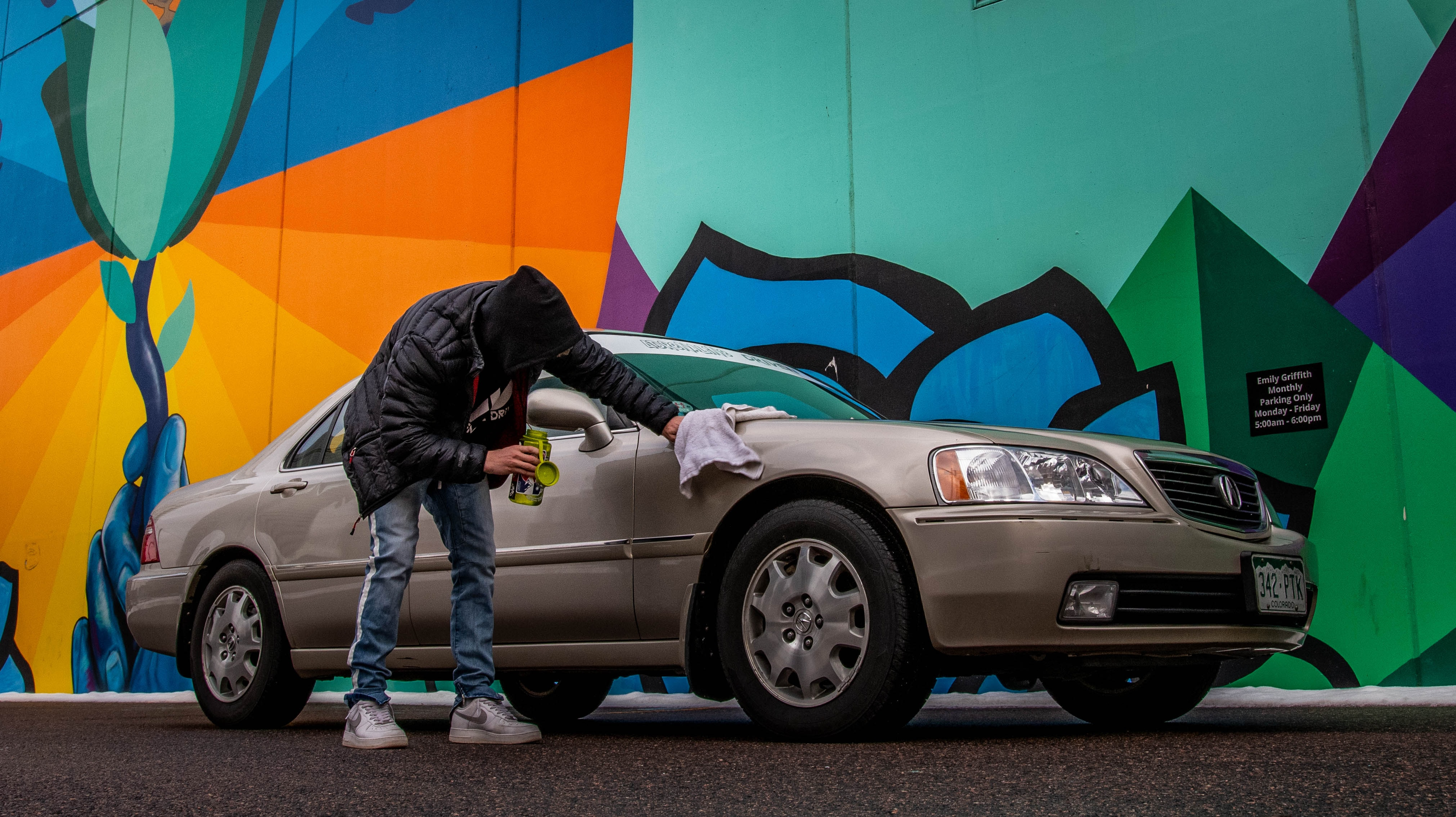 Young adult with sedan near multicolored mural