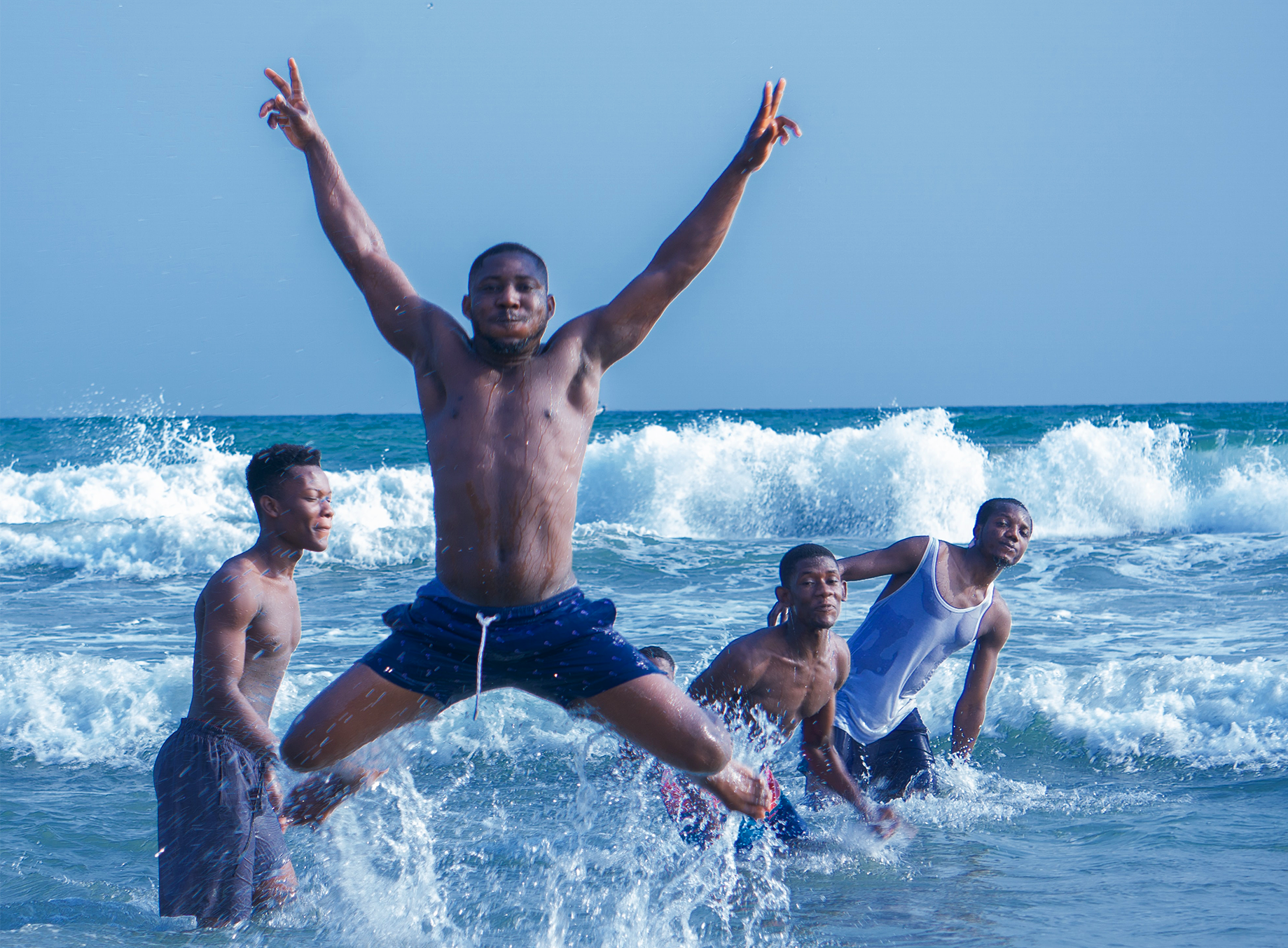 Four Black men playing and jumping in ocean