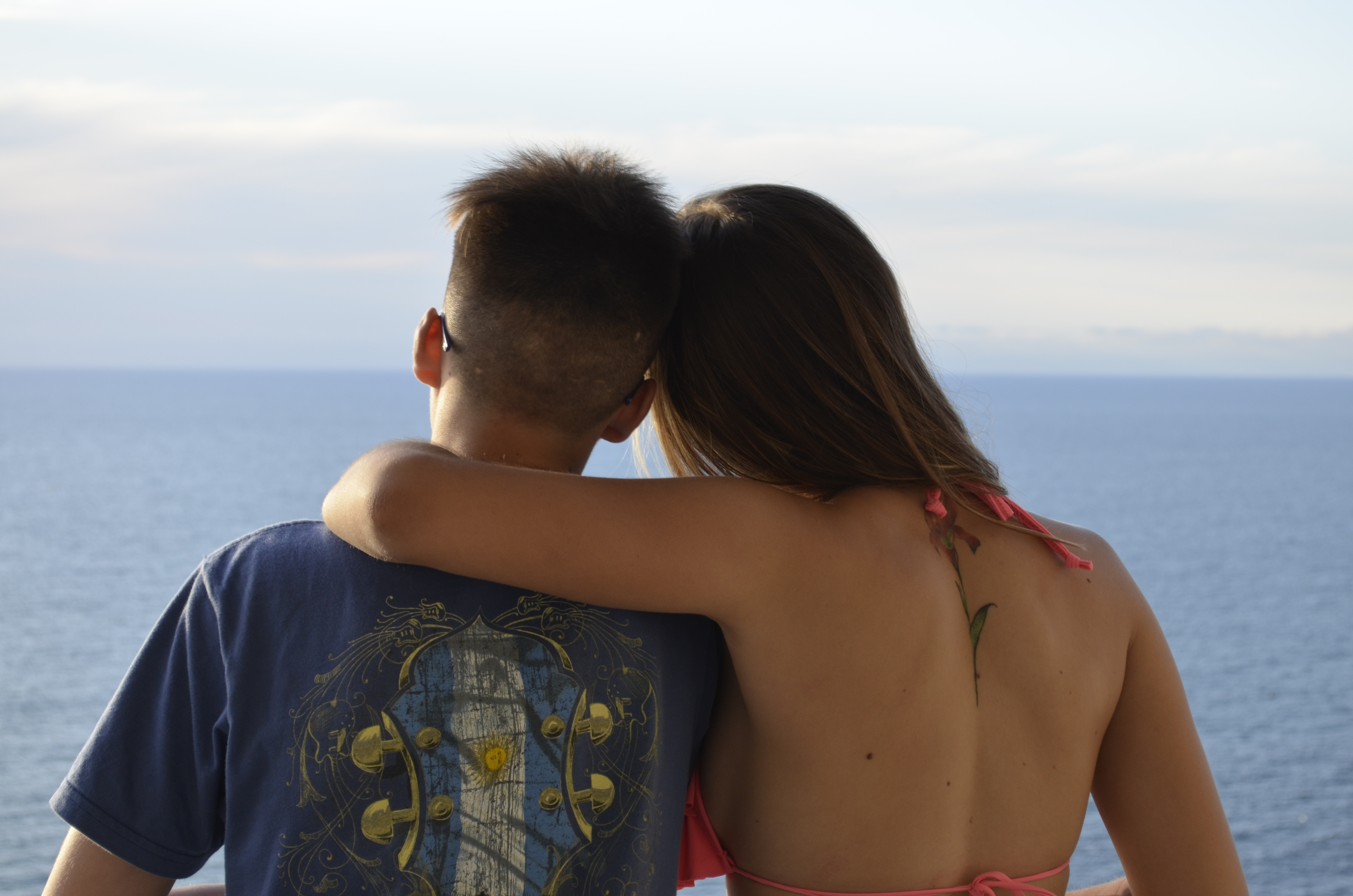 Couple with arms around one another, gazing at ocean