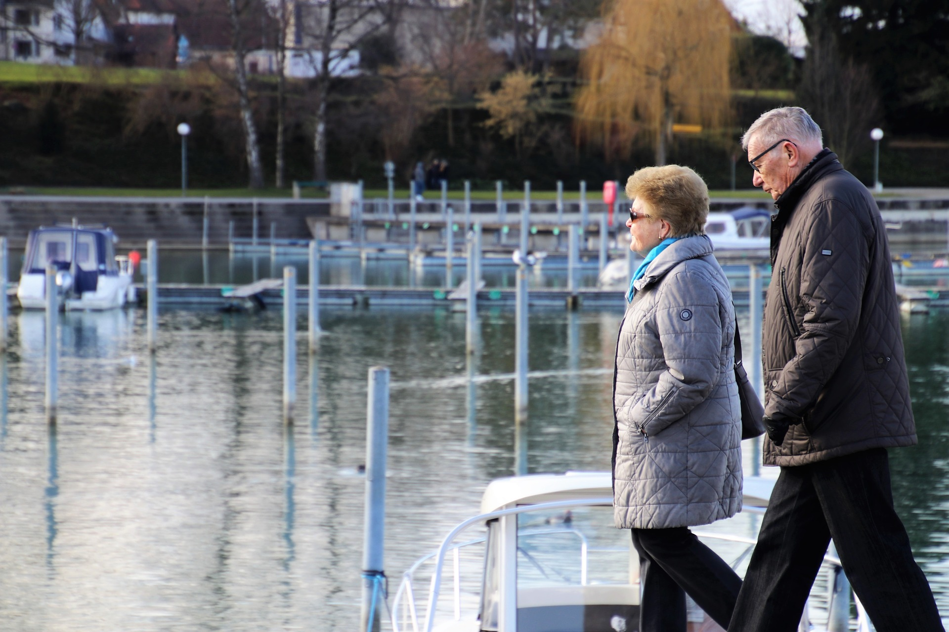 Older white couple walking by lake