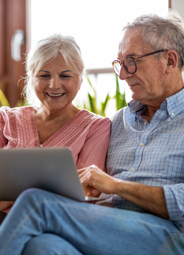 Senior couple sitting together and working on laptop