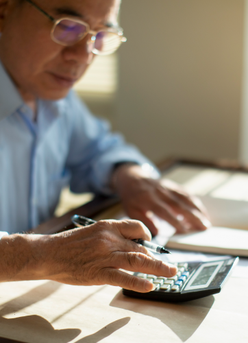 Man working on desk with calculator
