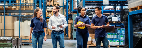 Four workers at a warehouse walking