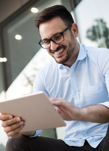Man in glasses smiling while using computer tablet
