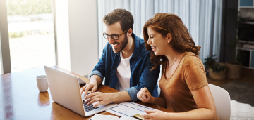 Man and woman smiling while working on laptop