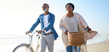 Couple smiling and walking on the beach with their bikes