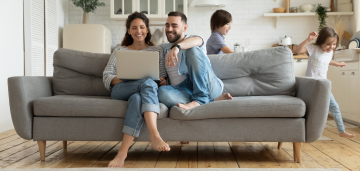 Couple smiling and sitting on the couch with their laptop