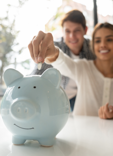 Happy woman putting coin in blue piggy bank