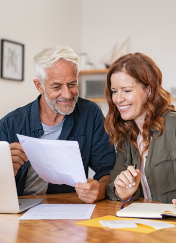 Man and woman looking at a document together and smiling