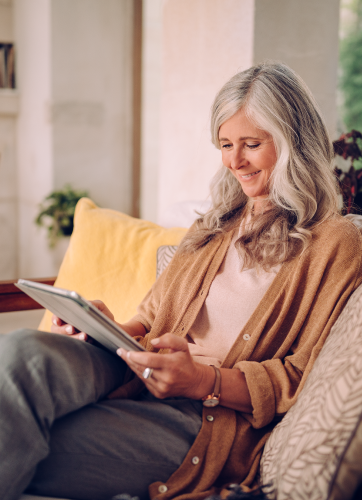 Woman sitting on a couch and working on a tablet