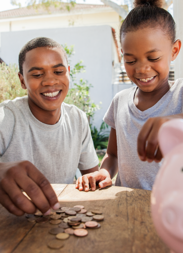 Two boys playing with coins on a table