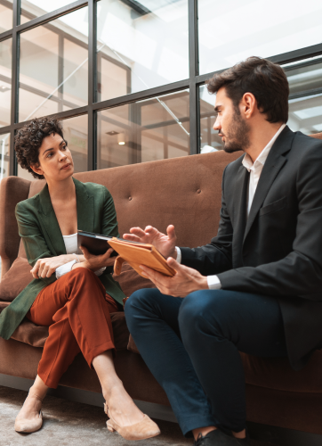 Business man and woman sitting on a couch at the office working