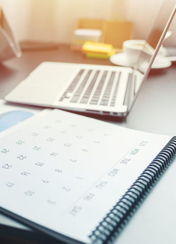 Calendar and laptop on a desk
