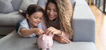 Happy mother and son put coins in a pink piggy bank