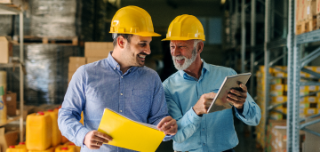 Two happy men with yellow construction hats working together.