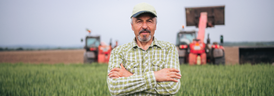 Man standing in a field with two trackers behind him