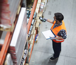 Worker holding a cellphone and notebook inside a warehouse