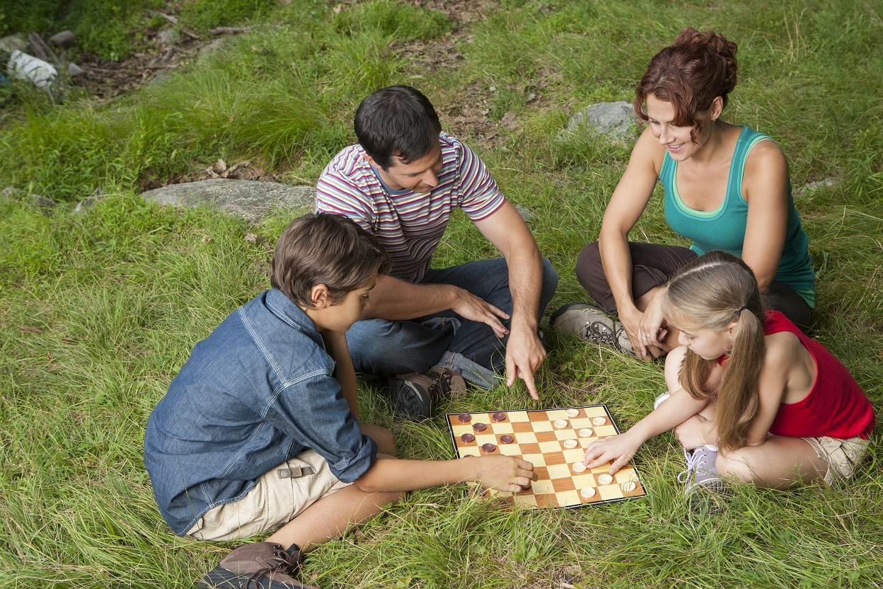 Parents sitting on the grass with their kids playing checkers
