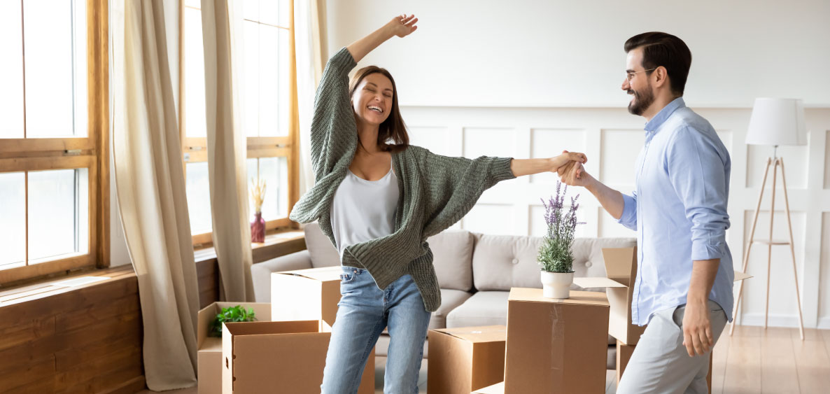 Happy woman dancing with hands in the air while man holds her hand