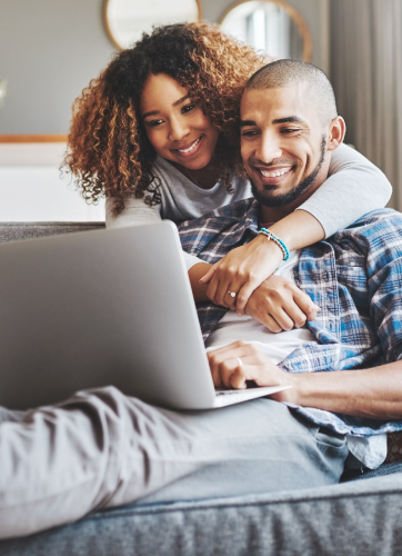 Woman putting her arm around a man while he's sitting on a couch with his laptop
