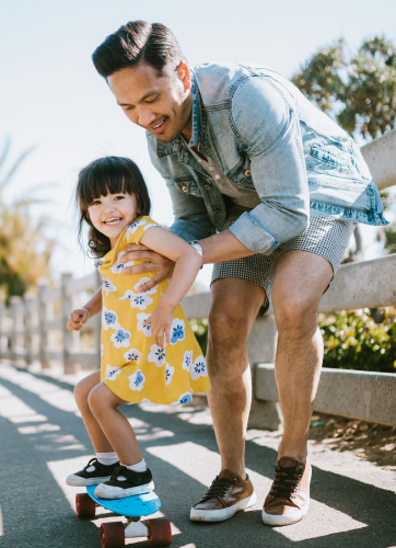 Father teaching his young daughter how to skateboard