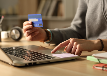 One hand on credit card and the other on laptop
