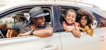 Man driving car with his wife and children inside