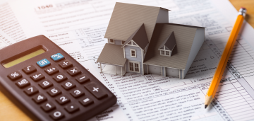 Calculator and toy mortgage on top of a tax form