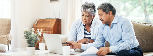 Senior couple sitting together in their living room with a laptop and papers