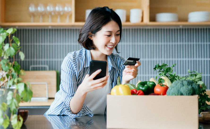 Happy woman holding a credit card and a cell phone