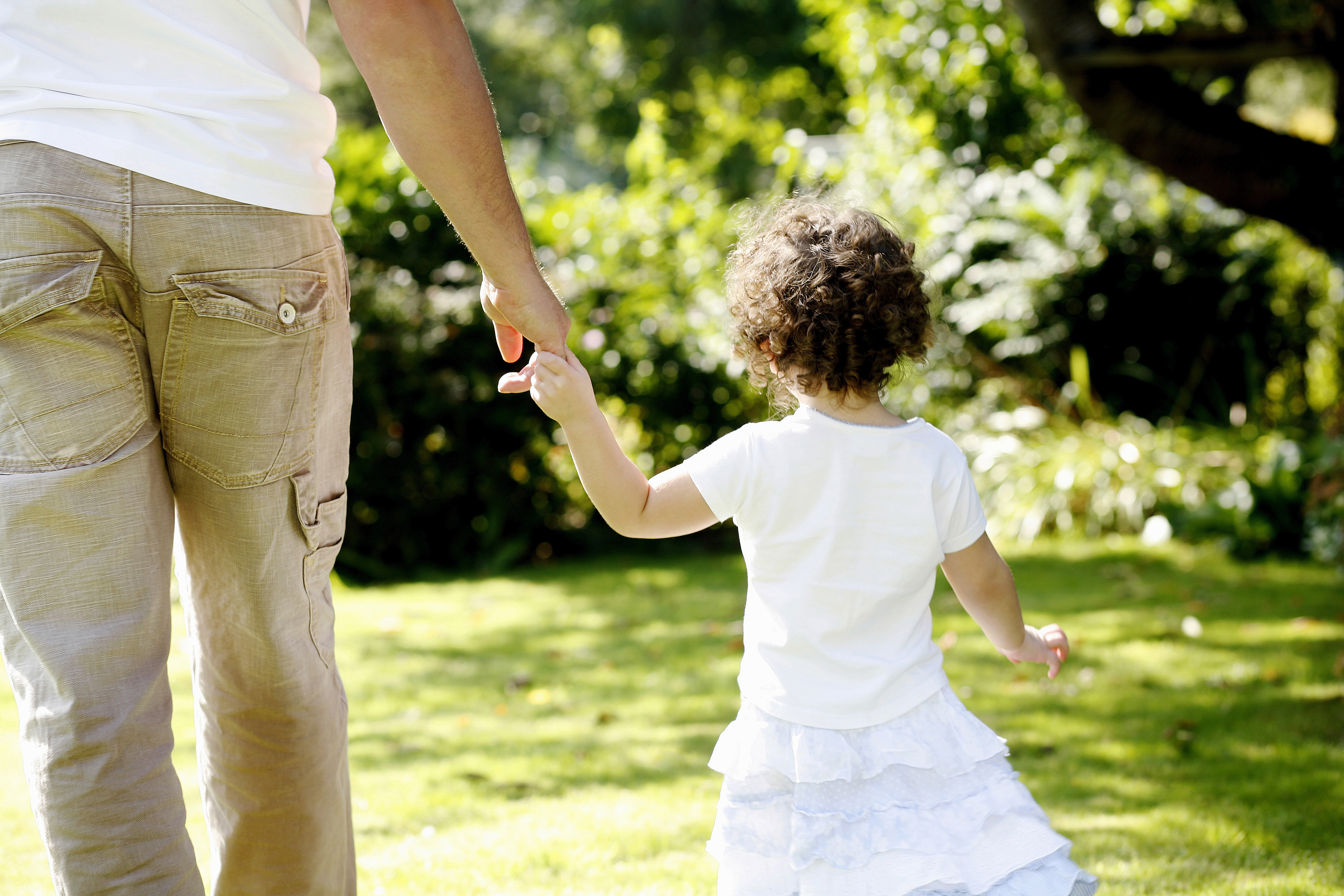Little girl in a white dress holding her father's hand