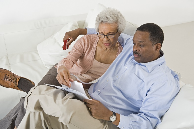 Senior couple sitting on a couch looking at their finances