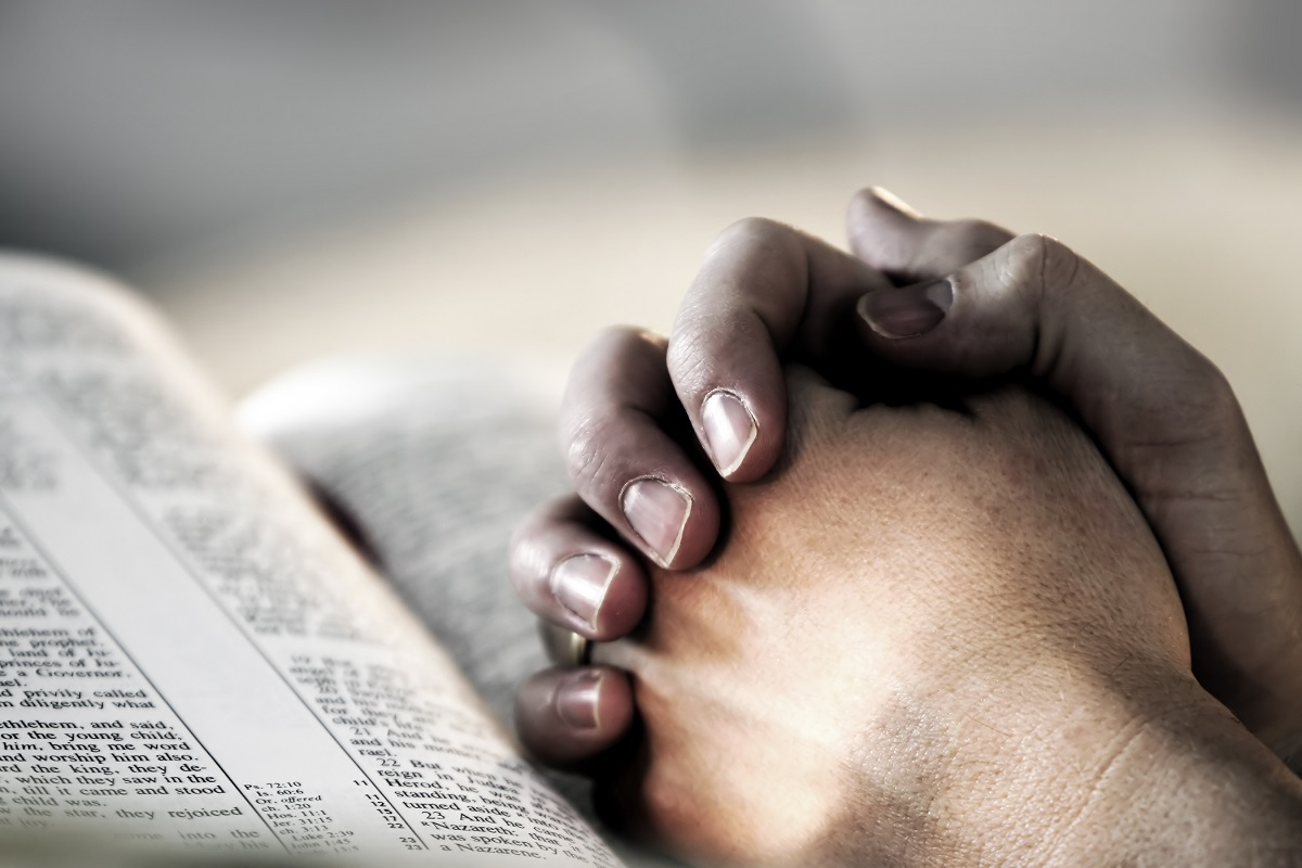 Praying hands on the Bible