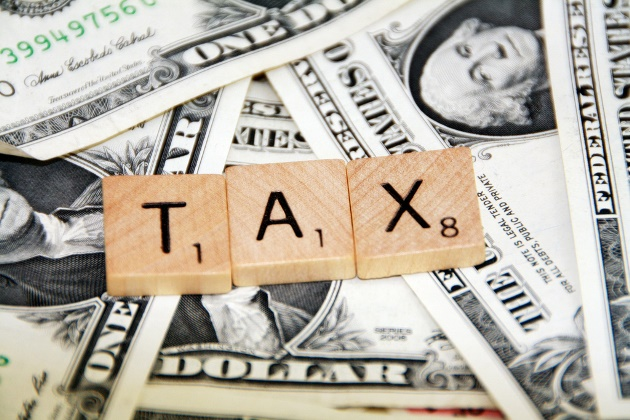 scrabble pieces spelling tax on top of dollar bills