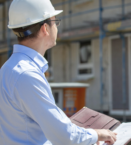 Construction worker looking at home being built