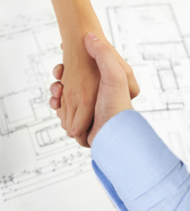 Two hands shaking in agreement over building plans for a new home