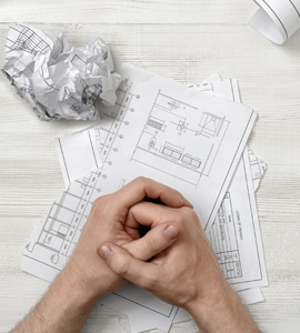 Clasped hands over building plans and crumpled paper on a table