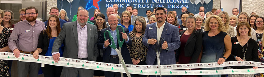 Bank employees and guests pose for a photo as the ribbon is cut for the Waxahachie branch