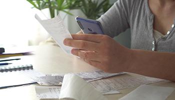 Woman looking at receipts at desk
