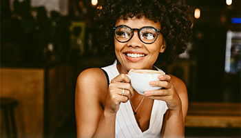 Woman smiling with coffee cup in  hand