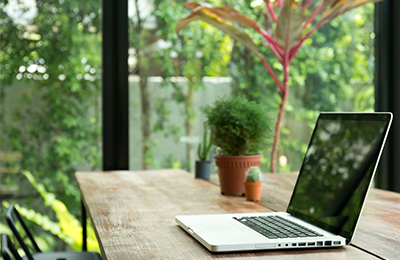 Computer sitting on desk surrounded by windows with greenery outside