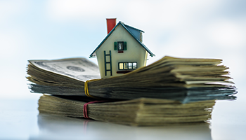 Small house model sitting on top of money stacks